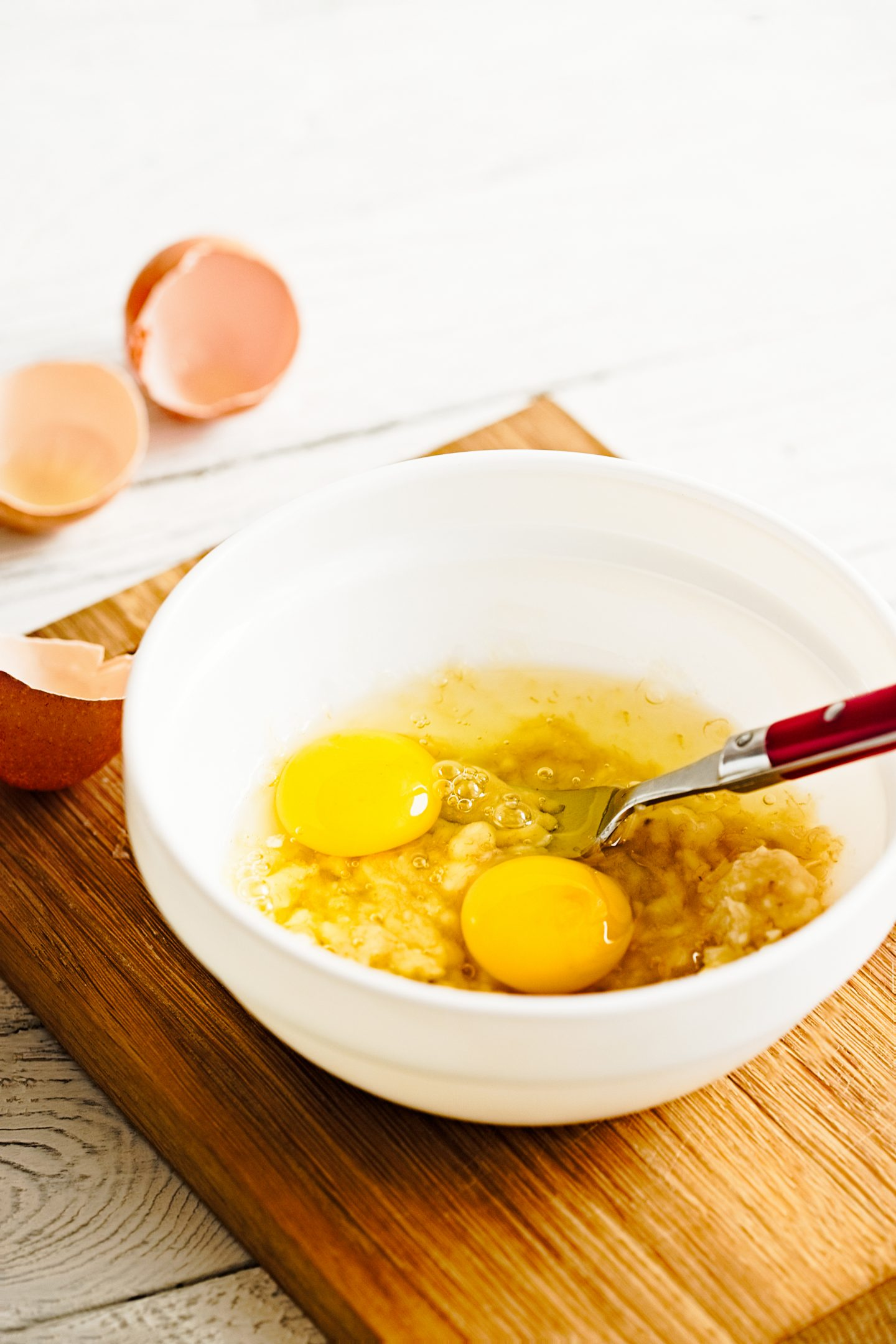 Mixing ingredients for paleo pancakes in white bowl - eggs, mashed banana on white rustic wooden background. Close up