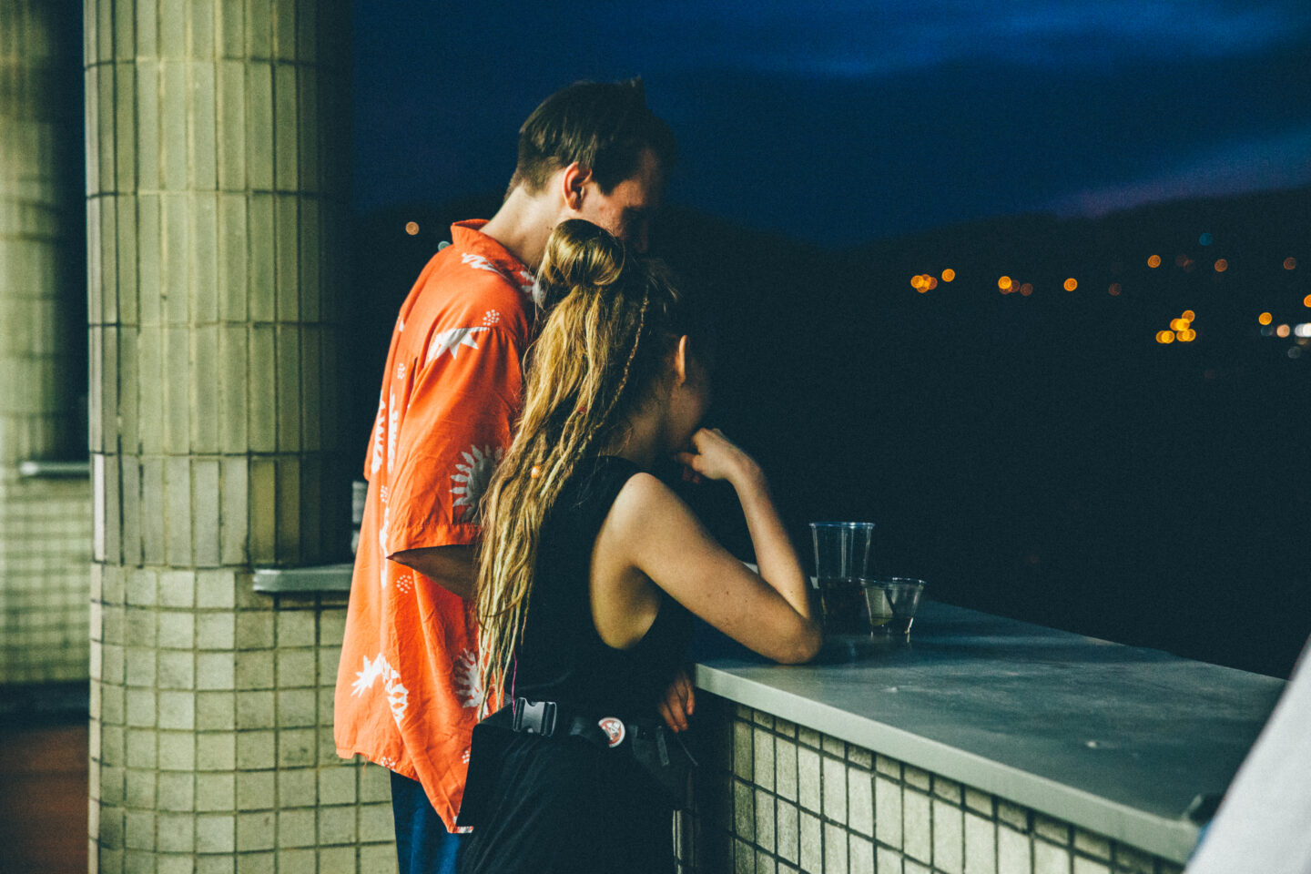 Young millennial couple from behind is talking and having fun in the night with view in the city.