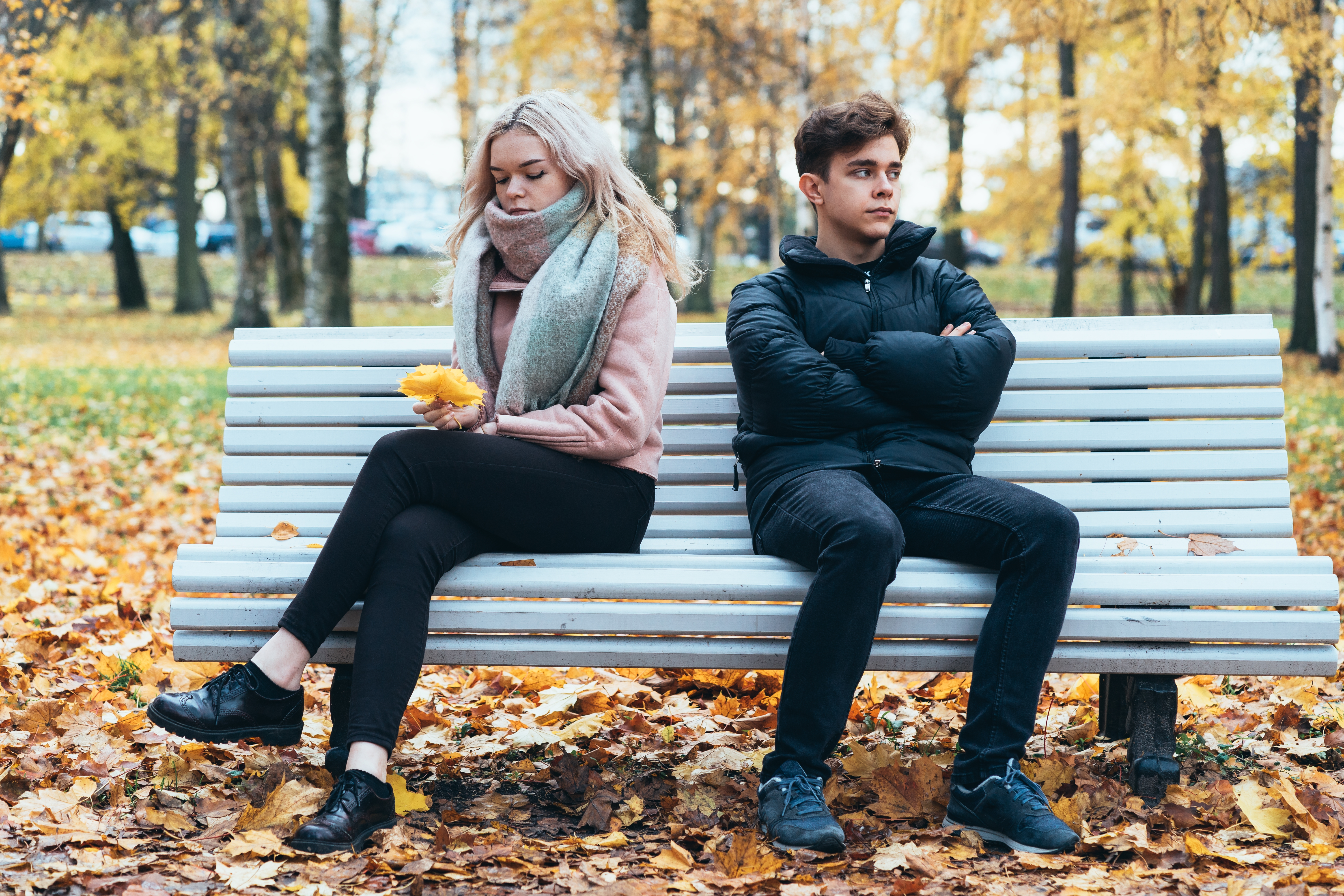 Two teenagers in love in quarrel. A brunette boy and blonde girl are sitting on opposite ends of benches, their backs to each other, do not want to talk and talk. Teenage Difficulty Concept
